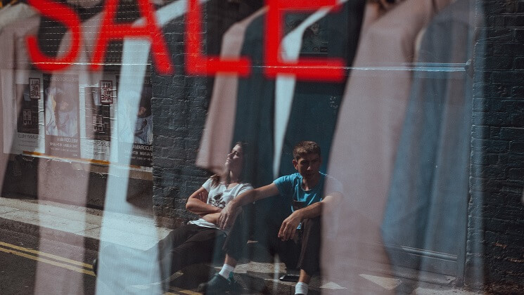 Business owners sitting outside a shop with a sale sign in the window