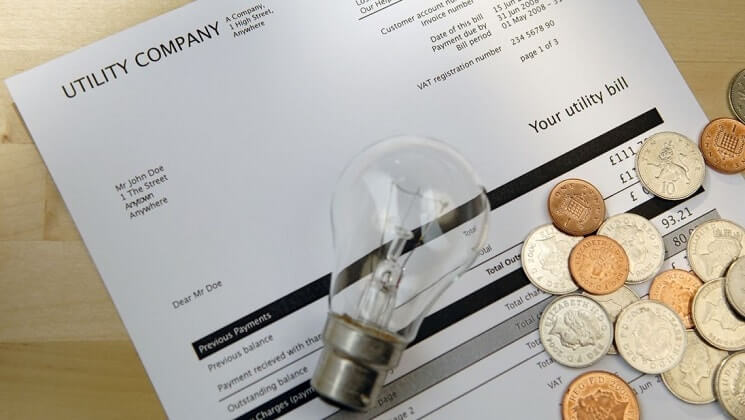 Paper with some coins and a lightbulb laid accross