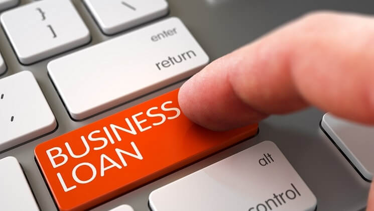 Finger hitting a shift key which instead of shift says BUSINESS LOAN